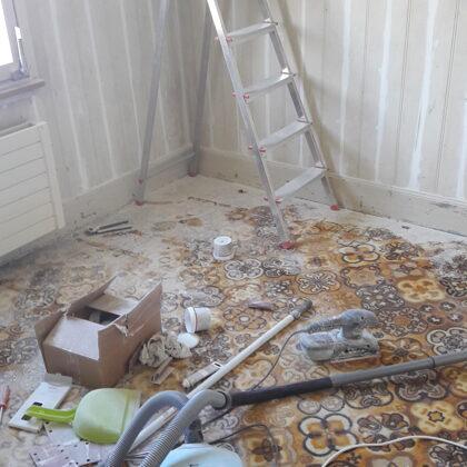 Zimmer mit altem Teppich, Risse in den Holzpaneelen wurden ausgespachtelt